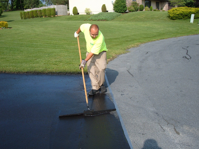 Crew applying sealcoat to driveway