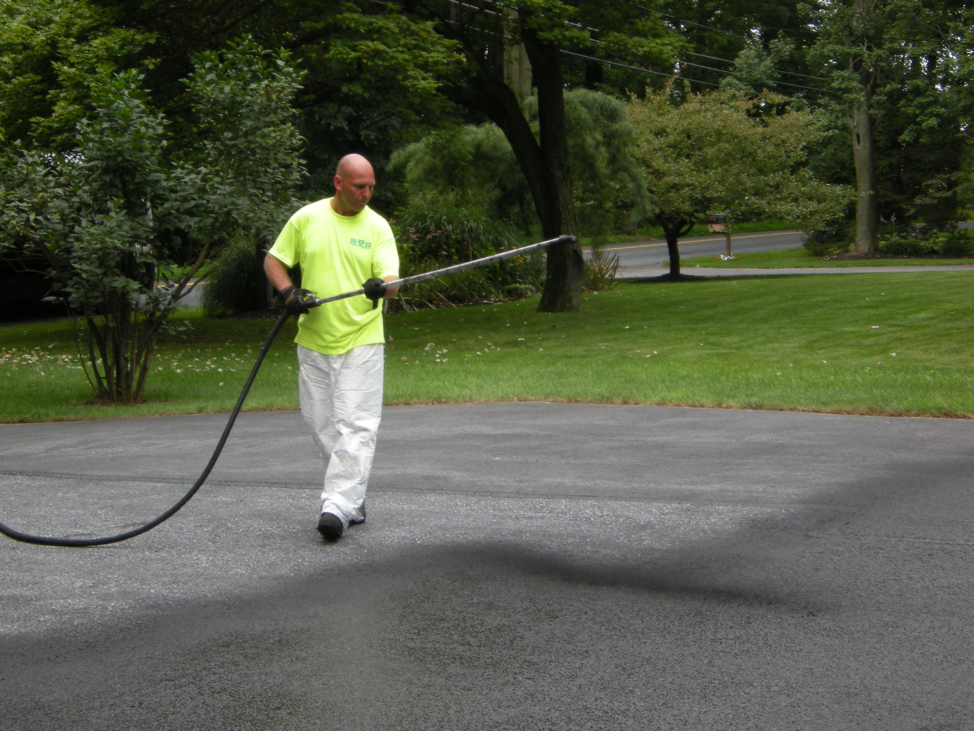 Asphalt paving crew using equipment to pave parking lot
