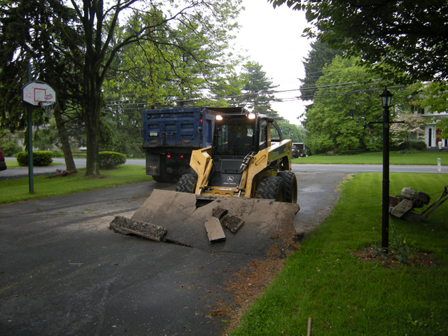 Crew removing old pavement with skid steer