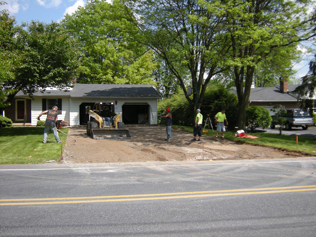 Crew preparing base for driveway to be installed