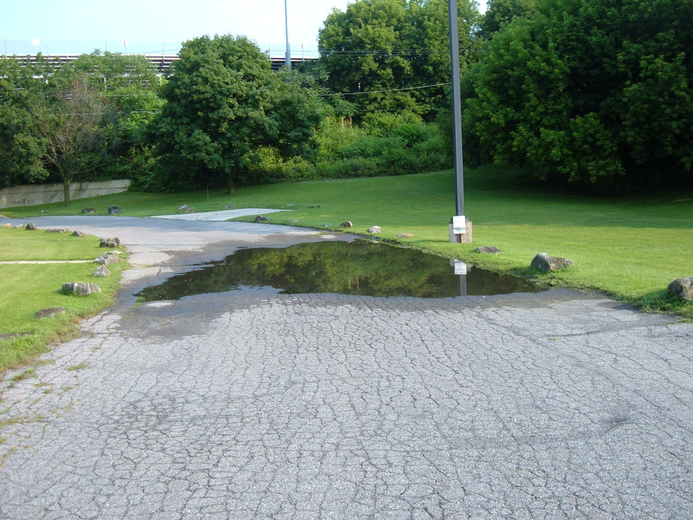 Uneven driveway with large water puddle and cracked pavement