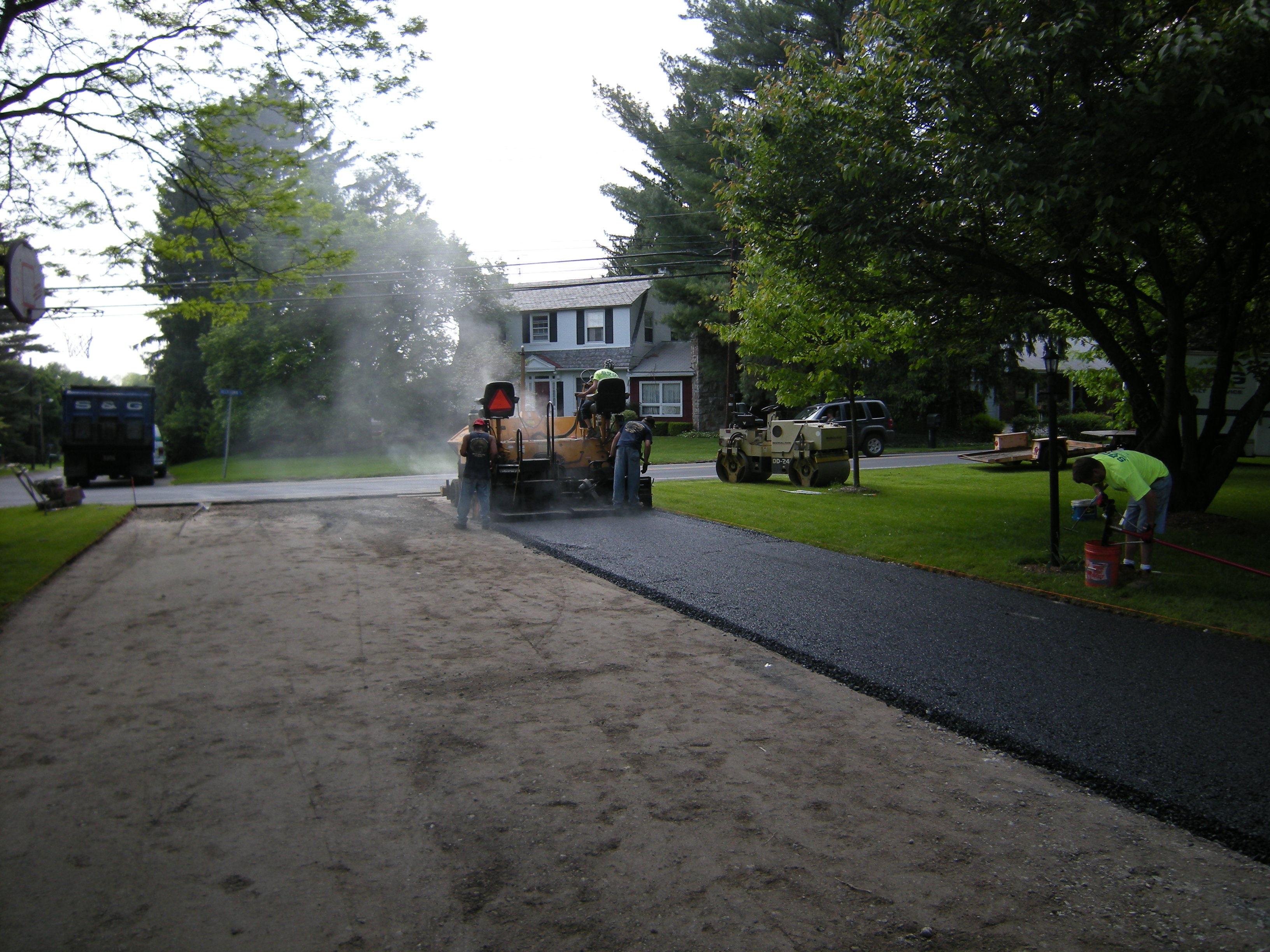 Crew using paving equipment to lay new pavement